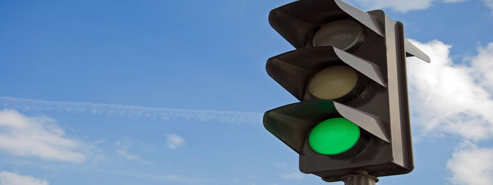 Green color on the traffic light with a beautiful blue sky in background